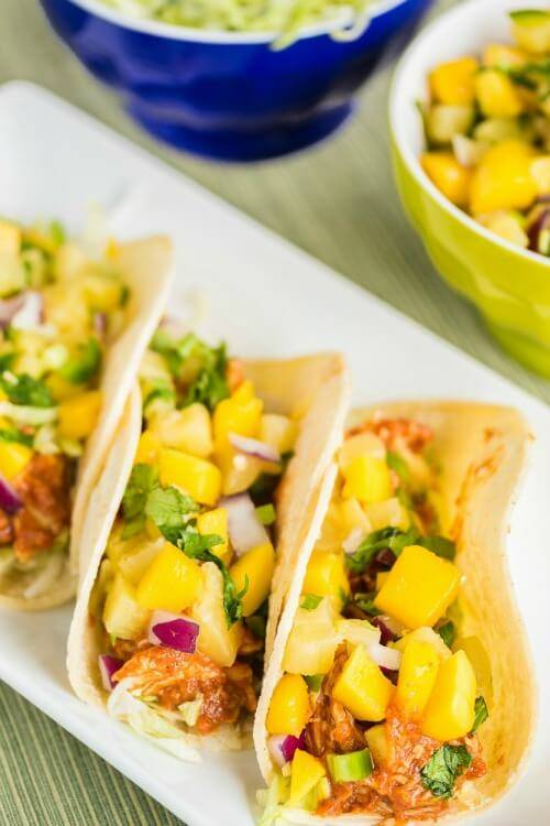 Corn tortillas filled with shredded lettuce, shredded barbecue chicken and topped with mango pineapple salsa