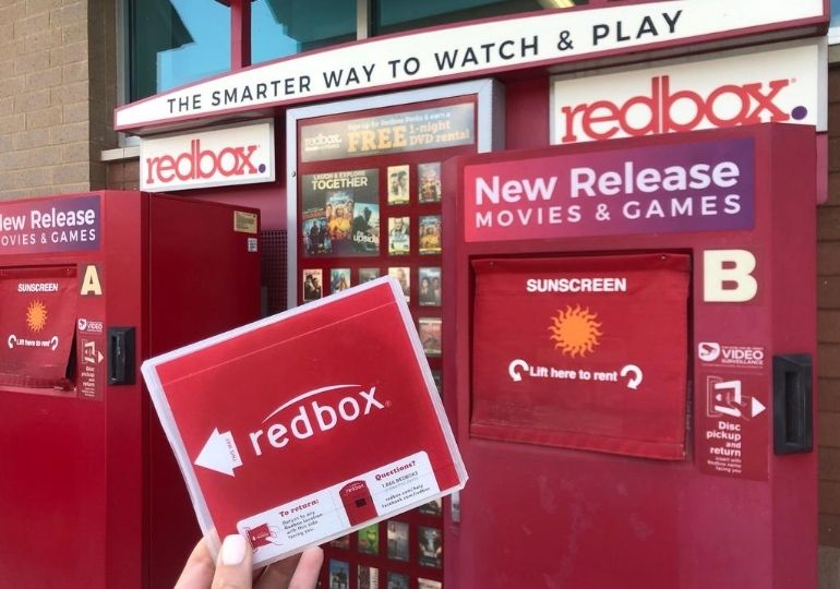 Redbox Movie Rental Codes - holding movie in front of kiosk